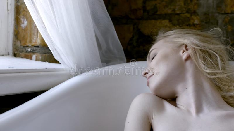 Beautiful girl sexy blonde in the morning posing in the bathroom. Action. Young blonde woman lying in the bath in the stock images