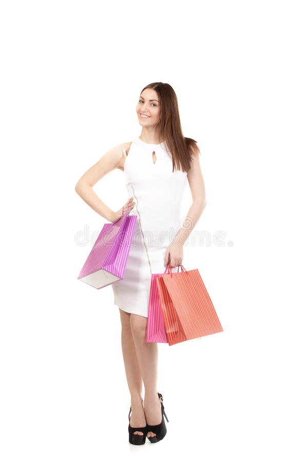 Beautiful girl with shopping bags, full length. Cheerful female shopping, young beautiful model on high heels holding colorful shopping bags, isolated on white stock images