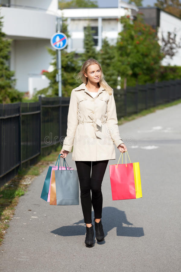 Beautiful girl with shopping bags. Walking down the street stock photography