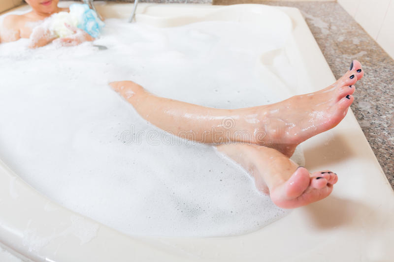 Beautiful girl showering and washing legs in bathtub. Beautiful girl showering and washing legs in bathtub stock images
