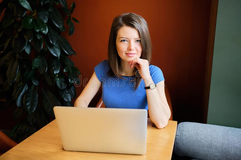 A beautiful girl sits in a cafe dressed in a blue dress behind a laptop. Freelancer concept. Close up stock image