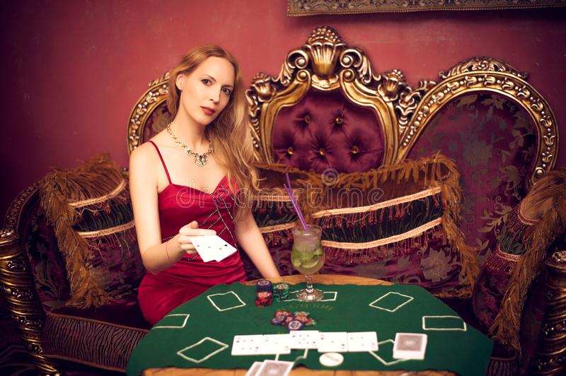 A beautiful girl sits on a couch playing poker on green cloth and holds playing cards in her hands. A beautiful girl among luxurious interiors sits on a couch royalty free stock photography