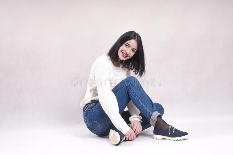 Beautiful girl sits on the floor in jeans studio a white sweater braces stock photo