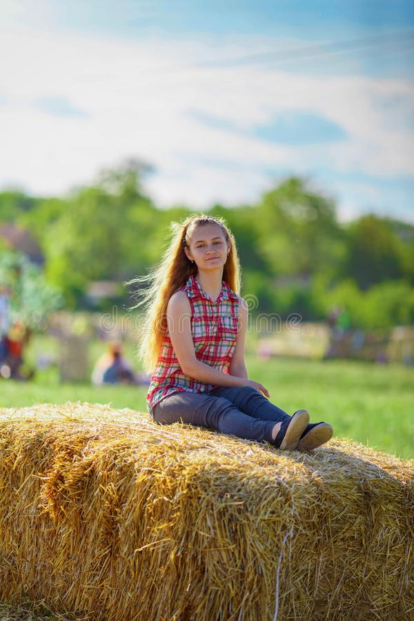Beautiful girl sits on a haystack royalty free stock photos