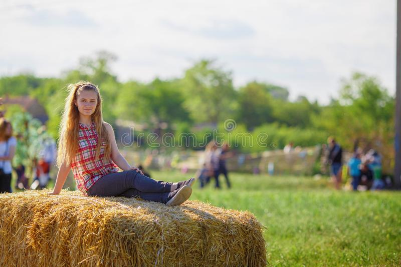 Beautiful girl sits on a haystack royalty free stock image