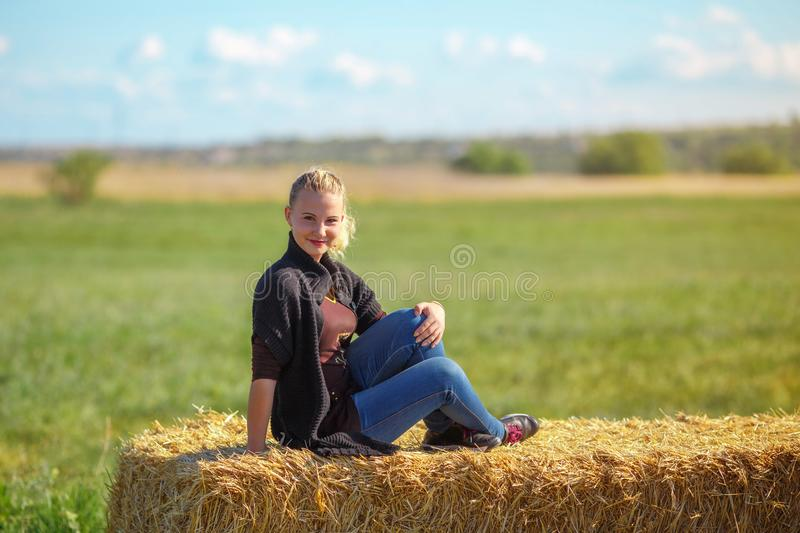 Beautiful girl sits on a haystack royalty free stock photography