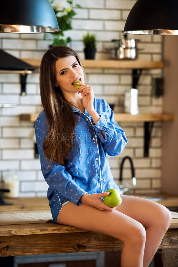 The beautiful girl sits on kitchen table with green apple in blue pajamas. The energy of morning, the magic of female beauty,. Youth and health stock photos