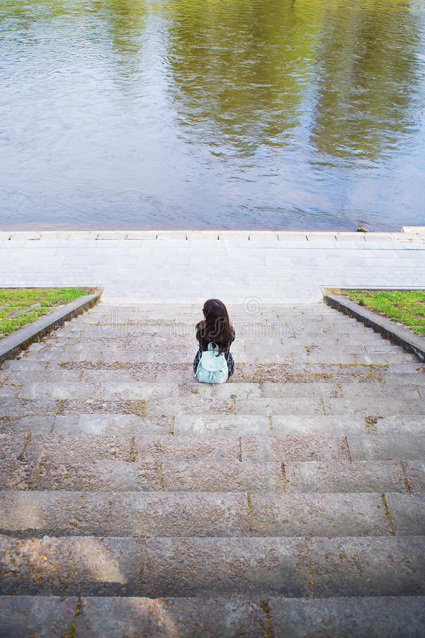 Beautiful girl sits and looks at the river Vilnius - Lithuania royalty free stock photos
