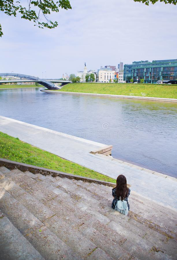 Beautiful girl sits and looks at the river Vilnius - Lithuania royalty free stock photo