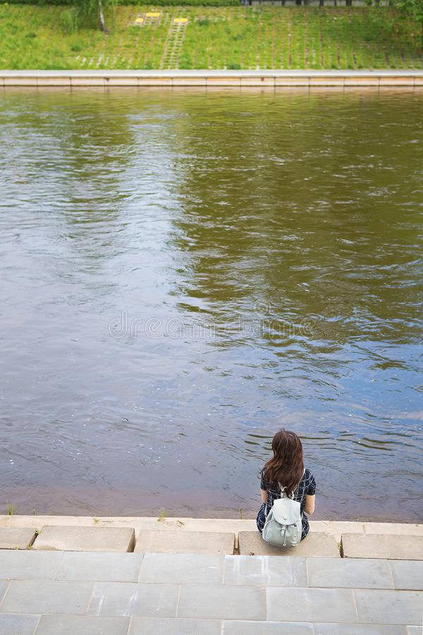 Beautiful girl sits and looks at the river Vilnius - Lithuania royalty free stock image