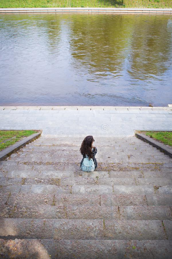 Beautiful girl sits and looks at the river Vilnius stock photography