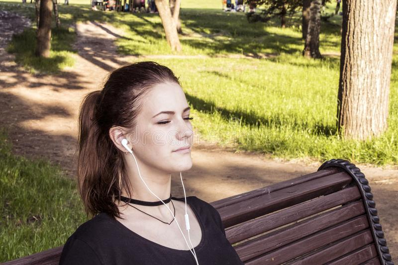 Beautiful girl sits on a park bench with closed eyes and listens to music on headphones royalty free stock photography