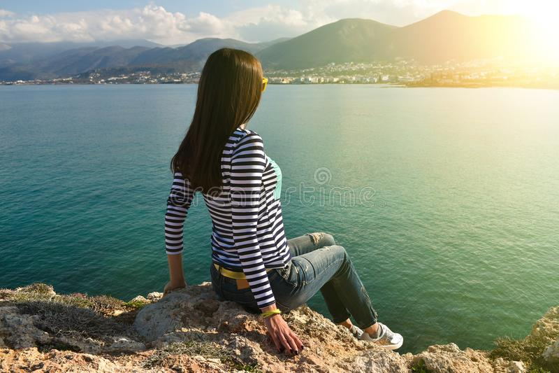 Beautiful girl sits on the rock stock photos