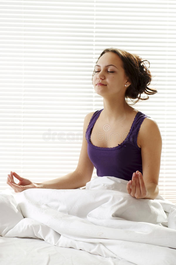 Beautiful girl sits up in bed. And meditate stock image