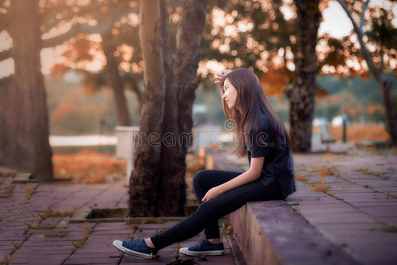 Beautiful girl sitting alone stock images