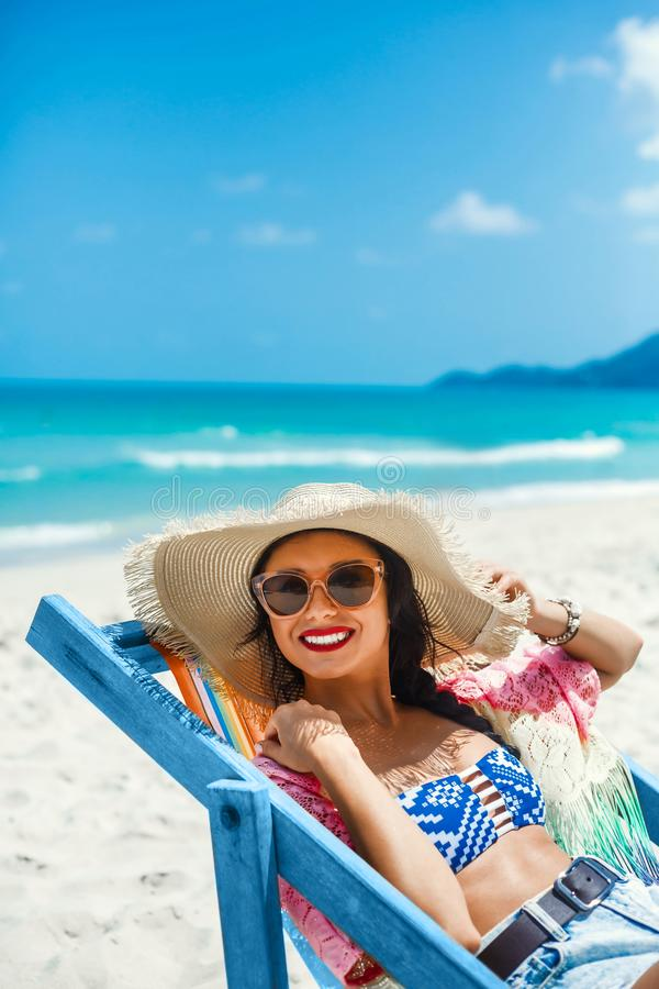 Beautiful girl sitting on beach by the sea in the color deck chair, dressed in a pair of straw hat with sunglasses, summer. Beautiful girl sitting on the beach royalty free stock photography