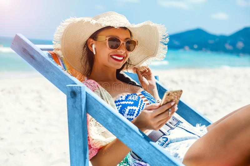 Beautiful girl sitting on beach by the sea in the color deck chair, dressed in a pair of straw hat with sunglasses, summer stock photography