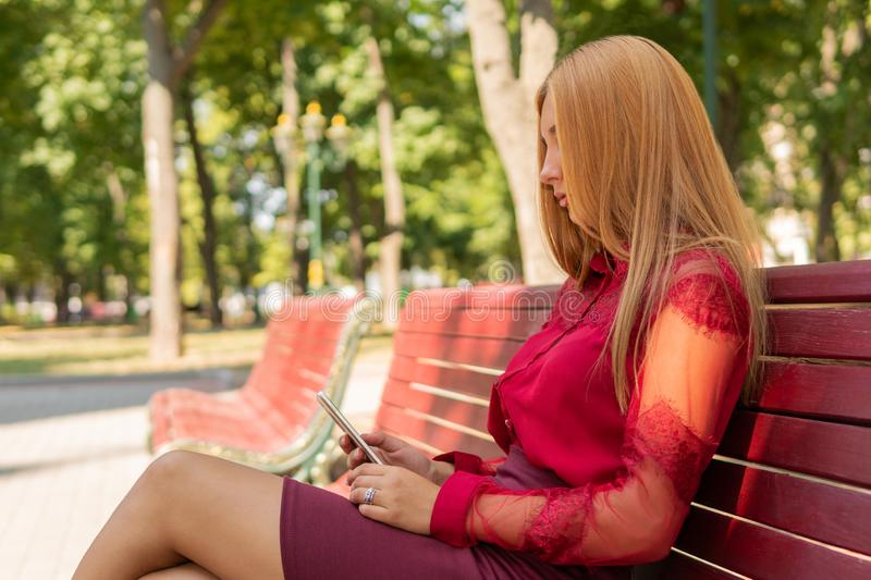 Woman uses a smartphone in the park stock photography