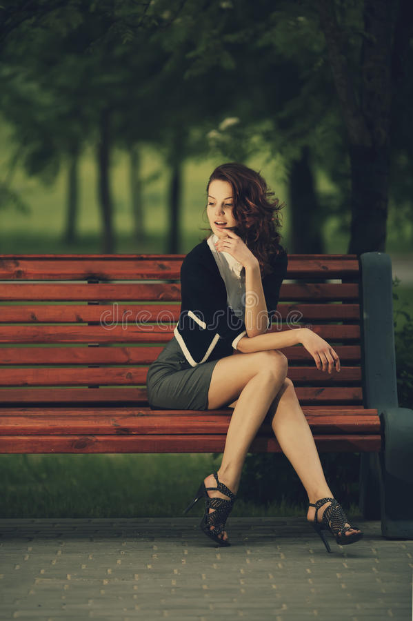 Beautiful girl sitting on bench in park stock image