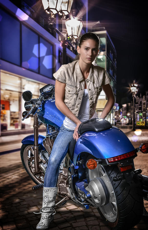 Beautiful girl sitting on a blue motorcycle, city street at night background. Young beautiful stylish woman sitting on a blue motorcycle. Outdoors. City street stock image
