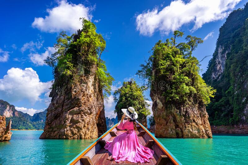 Beautiful girl sitting on the boat and looking to mountains in Ratchaprapha Dam at Khao Sok National Park, Surat Thani Province stock photos