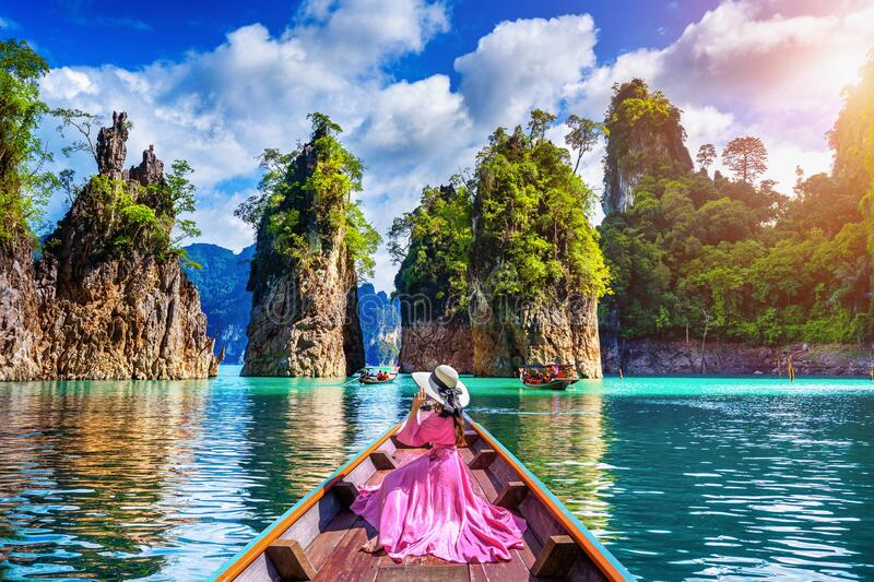Beautiful girl sitting on the boat and looking to mountains in Ratchaprapha Dam at Khao Sok National Park, Surat Thani Province royalty free stock photos