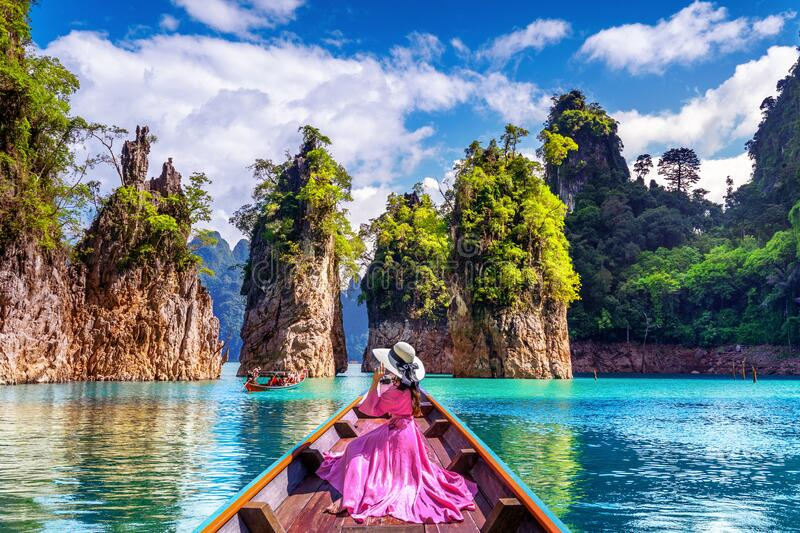Beautiful girl sitting on the boat and looking to mountains in Ratchaprapha Dam at Khao Sok National Park, Surat Thani Province royalty free stock photography