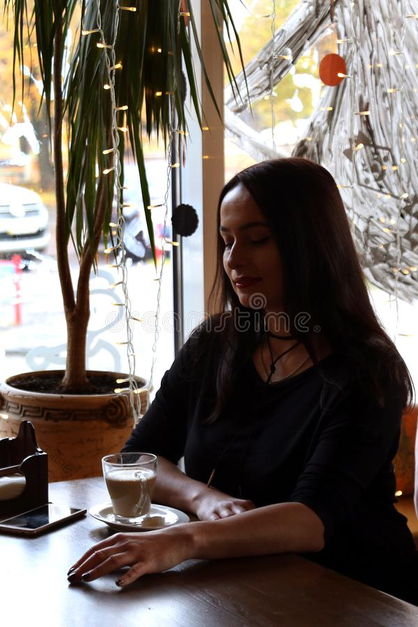 Beautiful girl is sitting in a cafe at a wooden table, enjoying drinking coffee from a glass cup. Silhouette in backlight from the. Window, low key stock image