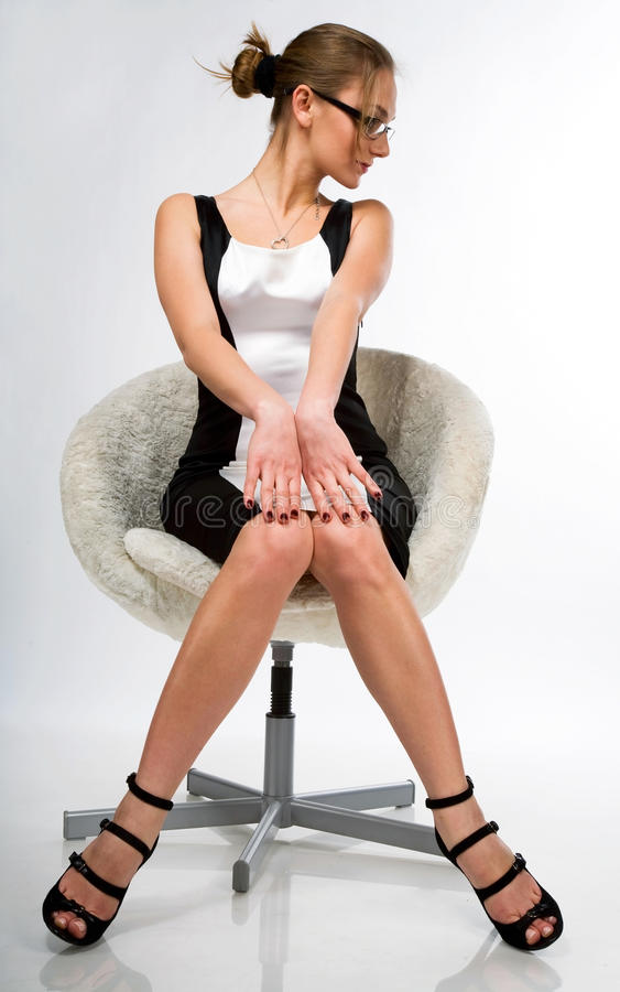A beautiful girl sitting on a chair royalty free stock images