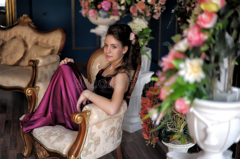 Beautiful girl sitting on a chair royalty free stock image
