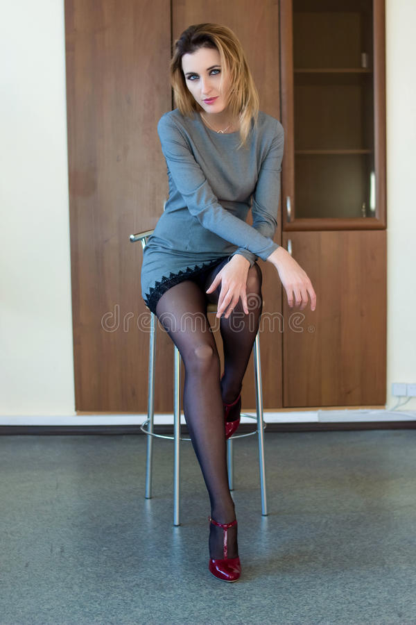 Beautiful girl sitting on a chair stock images