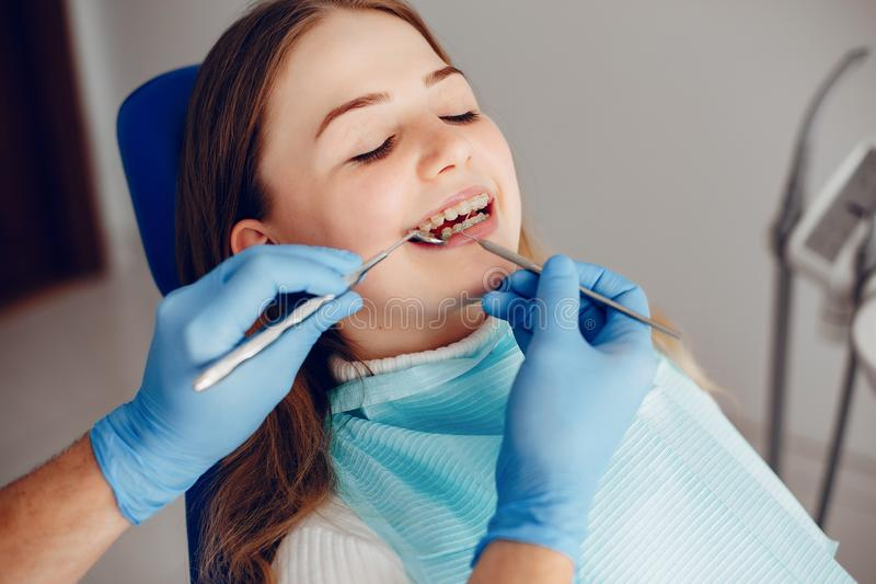 Beautiful girl sitting in the dentist`s office. Beautiful lady in the dentist`s office. Woman in a uniform stock image
