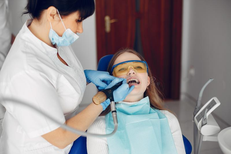 Beautiful girl sitting in the dentist`s office. Beautiful lady in the dentist`s office. Woman in a uniform royalty free stock image