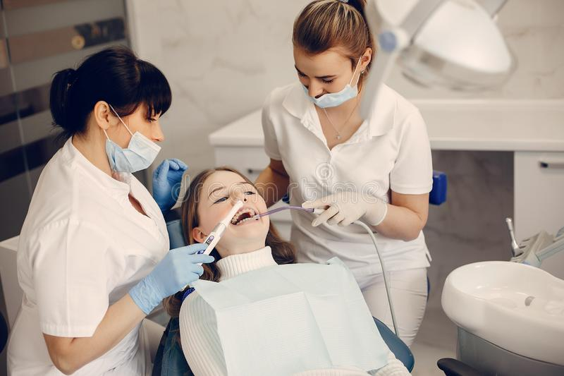 Beautiful girl sitting in the dentist`s office. Beautiful lady in the dentist`s office. Woman in a uniform stock photography