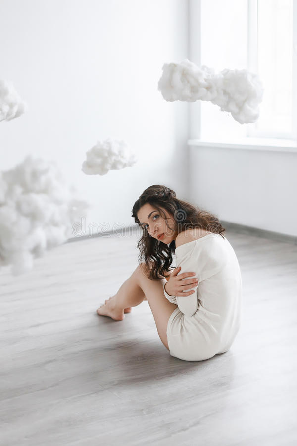 Beautiful girl sitting on the floor in the clouds. Picture of a beautiful girl sitting on the floor in the clouds royalty free stock photography