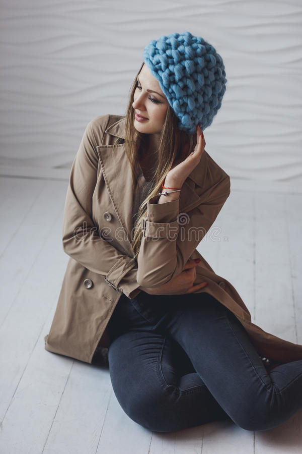 Beautiful girl sitting on the floor wearing knitted hat stock photography