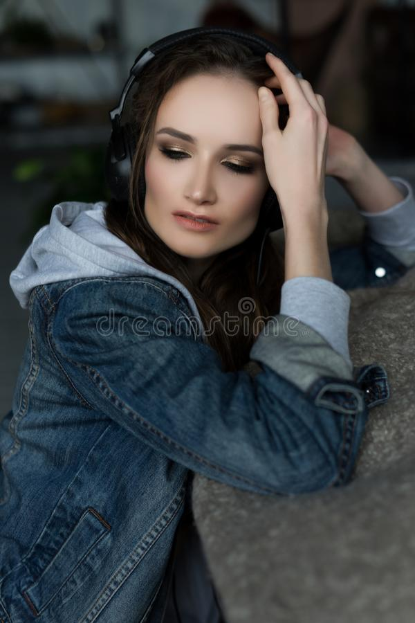 The beautiful girl sitting on a floor wearing underwear and a jeans jacket listens to music via earphones royalty free stock photo