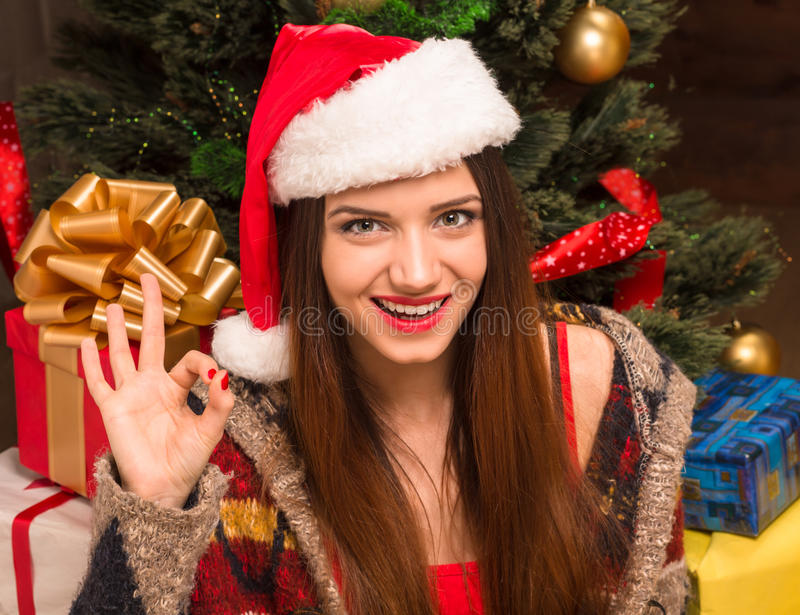 Beautiful girl sitting in front of New Year tree and showing okay sign stock images