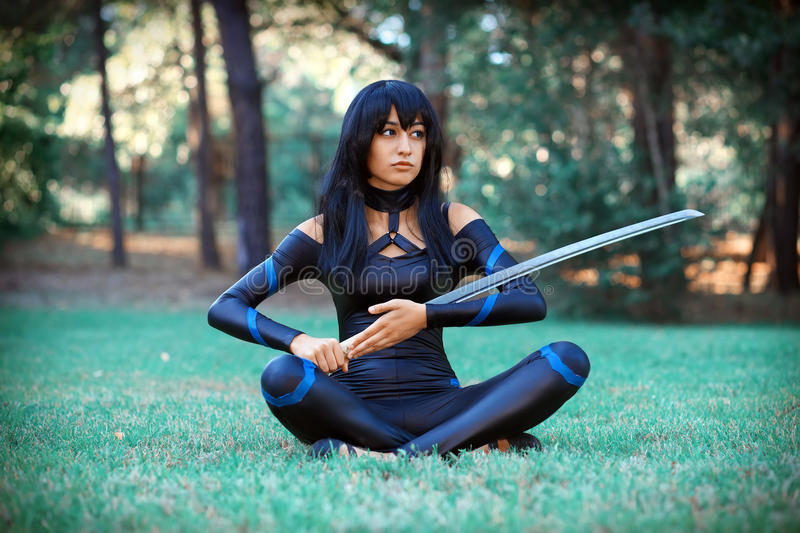 Beautiful girl sitting on the grass and holding samurai sword. Original cosplay character royalty free stock photography