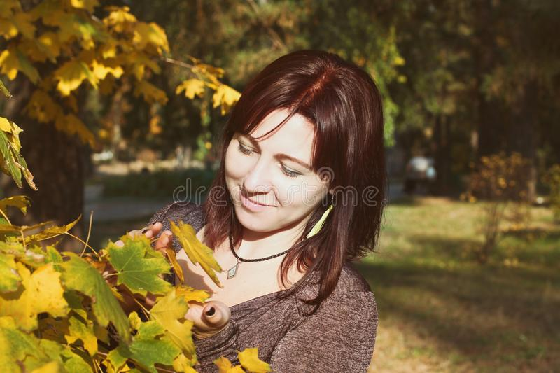 Beautiful girl sitting on the ground near the yellow leaves, girl autumn in nature on a Sunny day. brown hair color in royalty free stock photo