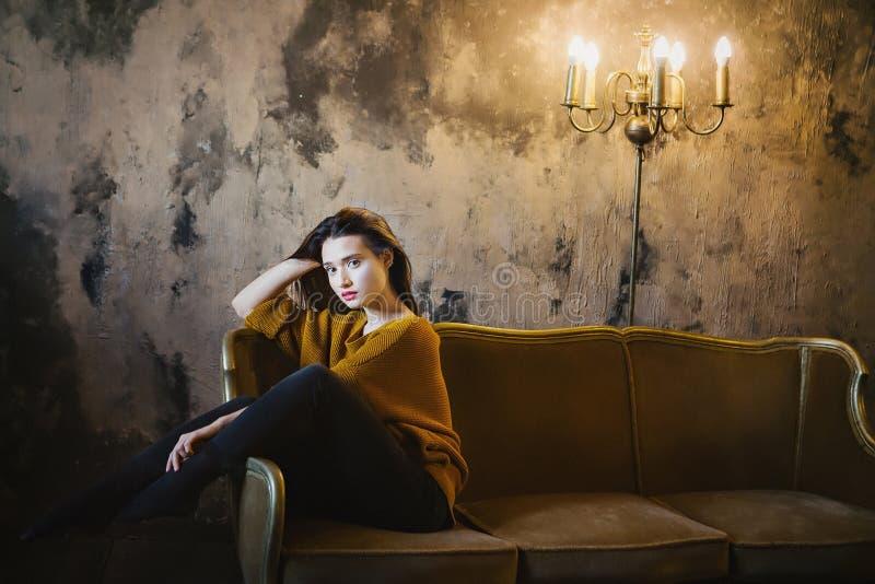 Beautiful girl sitting on a luxury sofa. Beautiful girl in a yellow sweater, sitting on a luxury sofa stock image