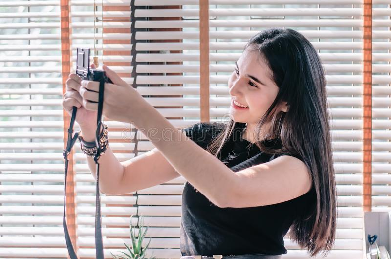 Beautiful girl sitting outdoors and taking selfie video for fashion blog. Woman holding compact camera in her hand ant taking royalty free stock photography