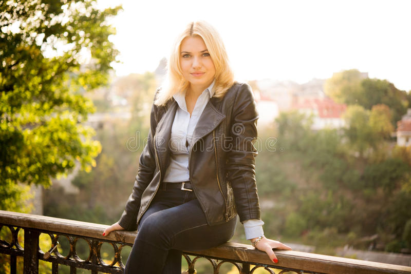 Beautiful girl sitting on the railing of the bridge royalty free stock images