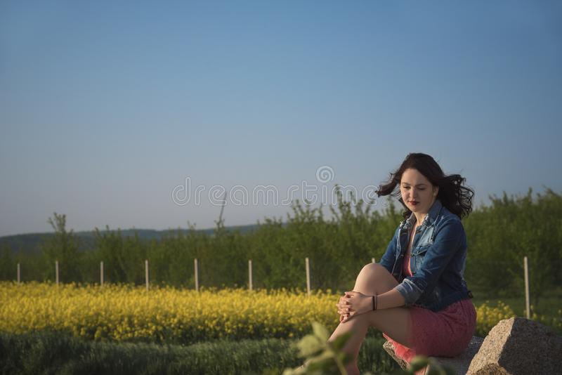 Beautiful girl sitting on a rock in nature royalty free stock photo