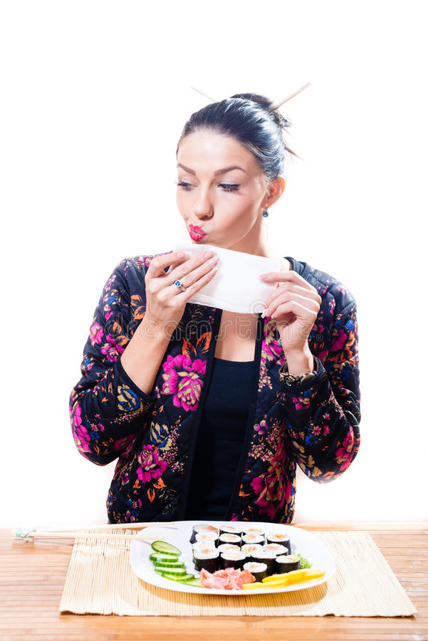 Beautiful girl sitting at the table and wipes her face with a towel or napkin. Nearby lies a plate of sushi, isolated on a white stock photo