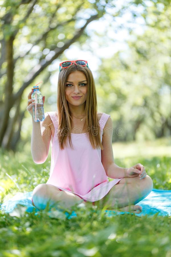 Beautiful girl sitting under the tree in nature and drinking fresh bottled water on sunny summer day. Girl sitting under the tree in nature and drinking fresh royalty free stock image