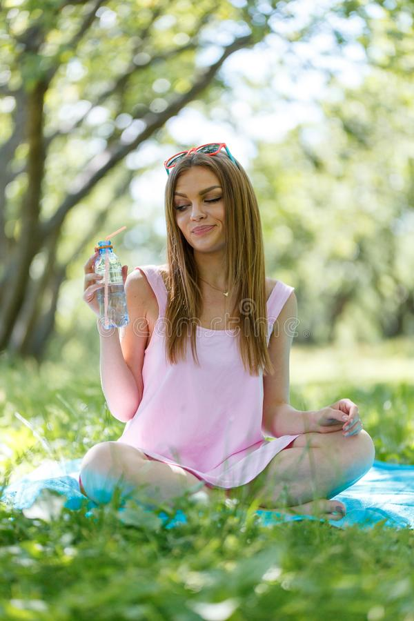 Beautiful girl sitting under the tree in nature and drinking fresh bottled water on sunny summer day. Girl sitting under the tree in nature and drinking fresh royalty free stock images