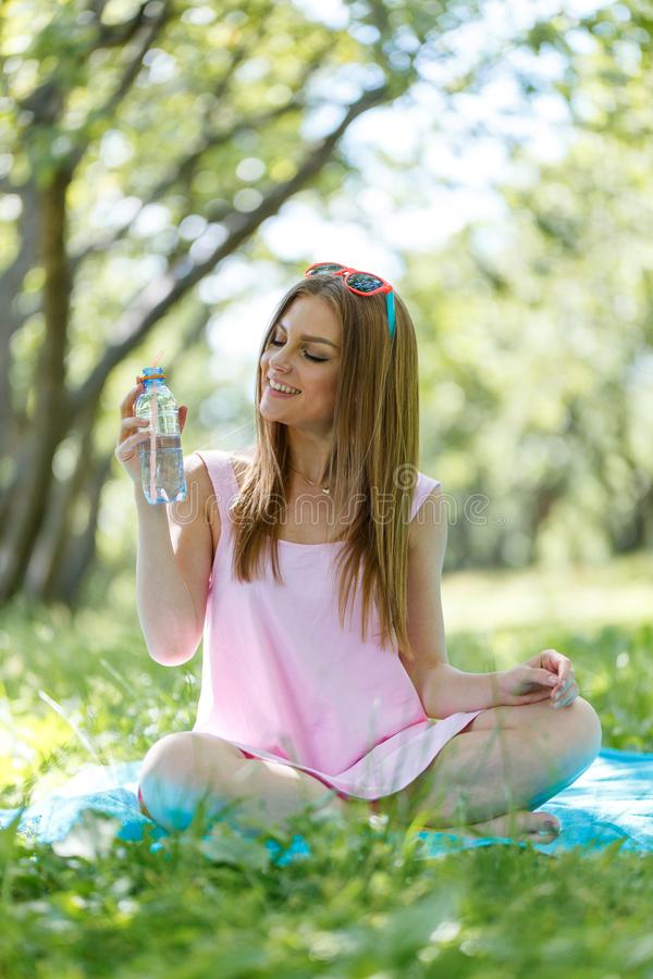 Beautiful girl sitting under the tree in nature and drinking fresh bottled water on sunny summer day. Girl sitting under the tree in nature and drinking fresh stock photos