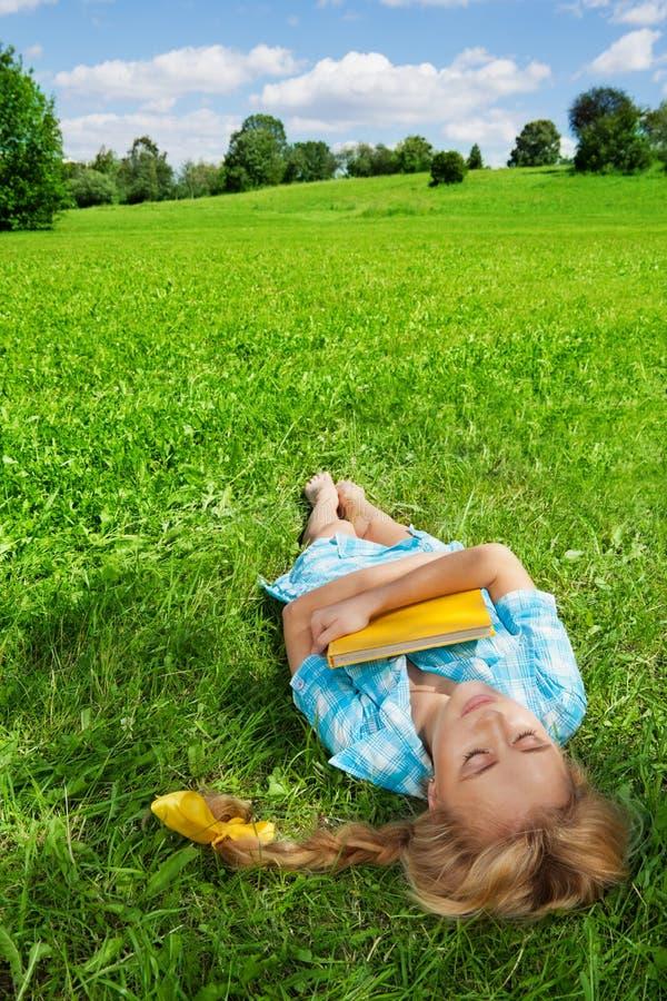 Beautiful girl sleeping on lawn stock photo