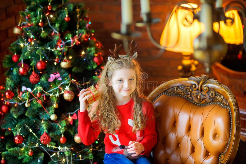 In anticipation of holidays. Beautiful girl with a small gift sits in a chair near a festive Christmas tree stock images